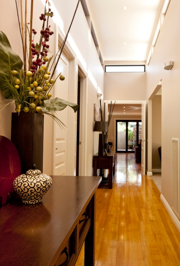 Entrance hall of new showcase home, with polished floorboards, downlighting, and elegant decor.
